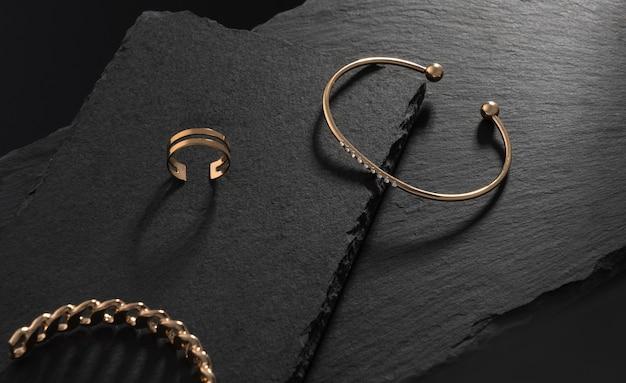 Diamant en gouden moderne armband en ring op zwarte stenen platen met kopieerruimte
