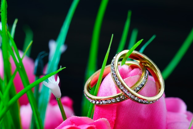 Diamanten trouwring rusten in een nep roze tulp close-up