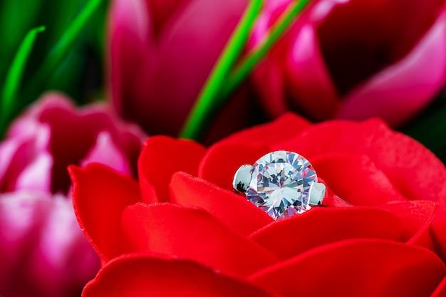 Diamanten trouwringen op rode rozen