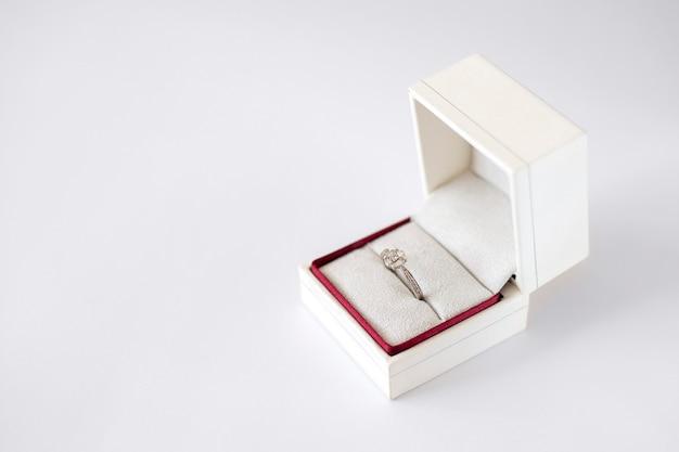 Diamanten verlovingsring in een witte doos op witte achtergrond voorstel om te trouwen