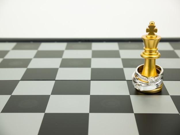 Diamantring met koning en koninginschaak op het bord, huwelijksconcept.