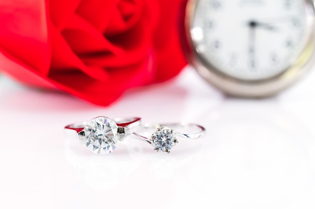 Diamond gem trouwringen met horloge op witte achtergrond