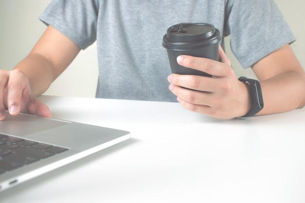 Dicht bij de handen van mensen die grijze t-shirts dragen, met behulp van een laptop op de tafel met een kopje koffie.