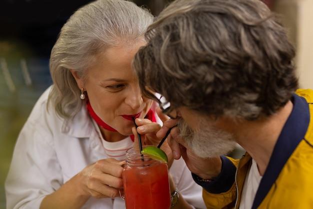 Dicht bij elkaar. gelukkig verliefde paar zitten in het café en drinken hun koude smoothie met twee rietjes uit één glas.
