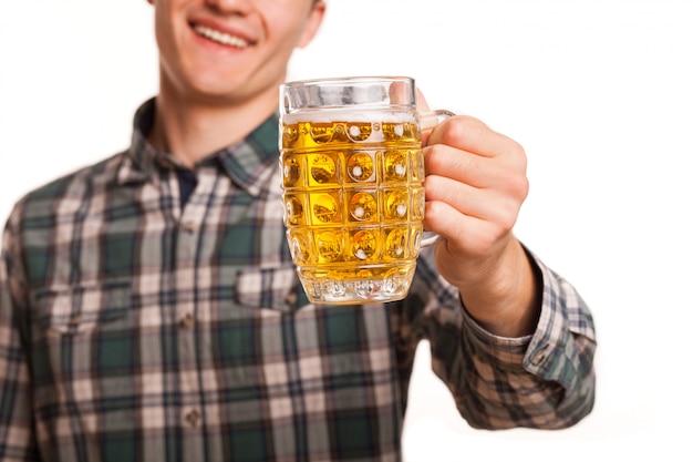 Dicht omhoog bebouwd van een glas bier in de hand van een gelukkige die mens op wit wordt geïsoleerd. vrolijke mens die gelukkig glimlacht, die bier aan de camera standhoudt. drinken, feesten concept