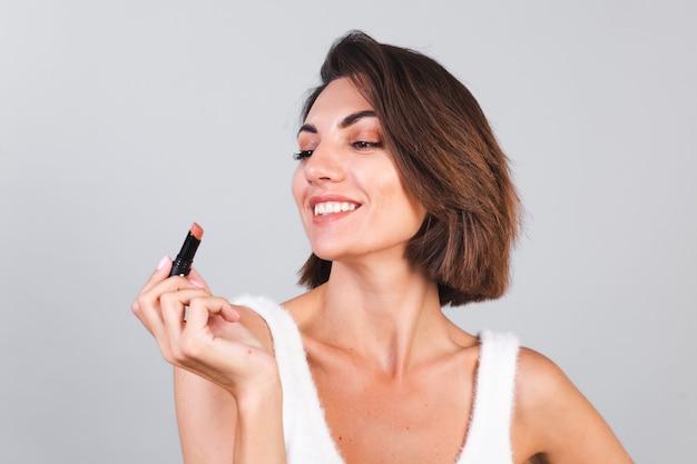 Dicht schoonheidsportret van vrouw met make-up en bruine lippenstift op grijze muur