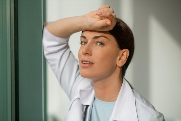 Dichtbij het raam. een donkerharige dokter die bij het raam staat en nadenkend kijkt