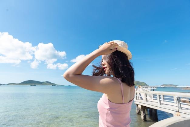 Dichtbij van aziatische vrouwentan huid die roze mouwloos onderhemd draagt en strohoed houdt.