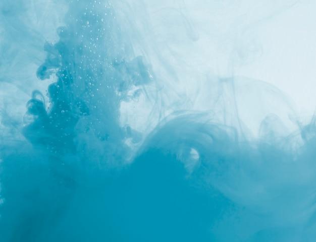 Dichte blauwe wolk van waas in vloeistof