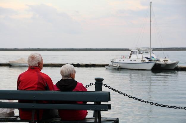 Dichte mening van een eenzaam oud paar op de bank die de oceaan staart.