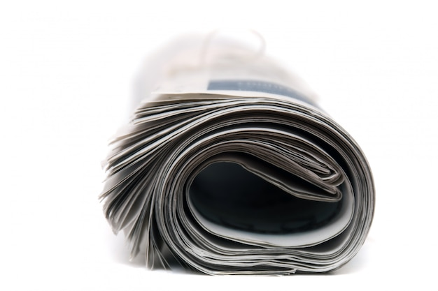 Dichte mening van een opgerolde krant met koord dat op een witte achtergrond wordt geïsoleerd.