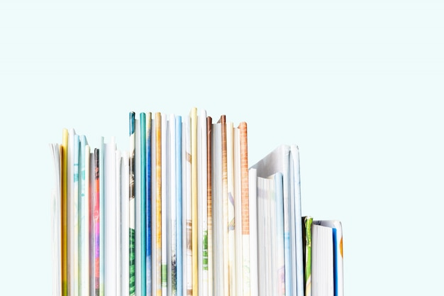 Dichte mening van stapel boeken van kinderen op een pastelkleur blauwe achtergrond.