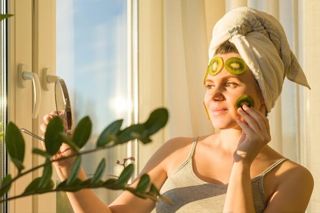 Dichte omhooggaand van de vrouw thuis dichtbij het venster met natuurlijk eigengemaakt fruit gezichtsmasker van kiwi op gezicht