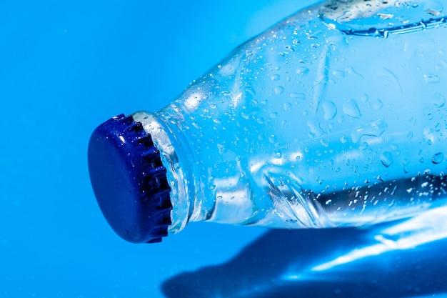 Dichte omhooggaand van de waterfles op blauw