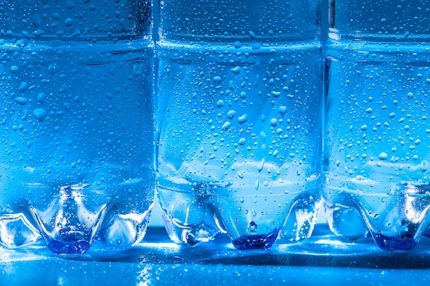 Dichte omhooggaand van de waterfles op donkerblauwe achtergrond