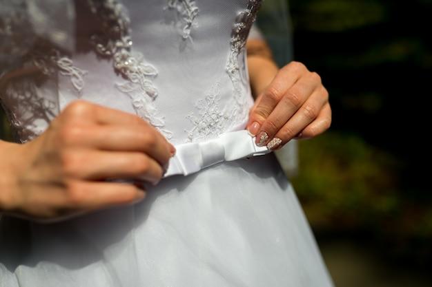 Dichte omhooggaand van een bruidkleding met een grote zijdeboog