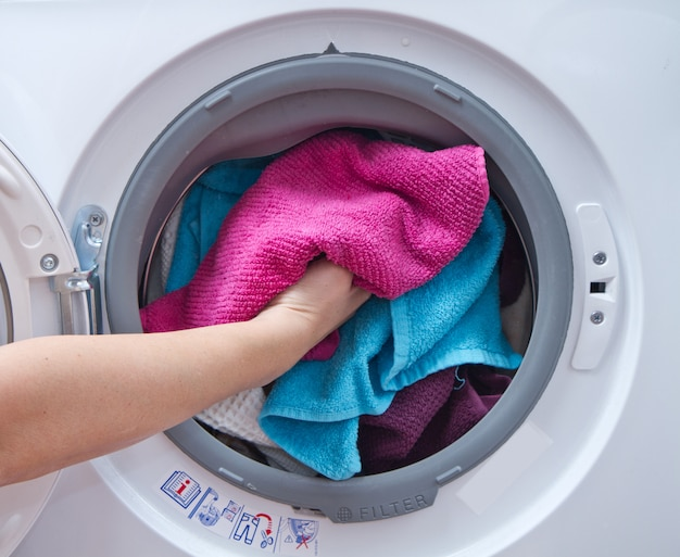 Dichte omhooggaand van een wasmachine die met kleren wordt geladen
