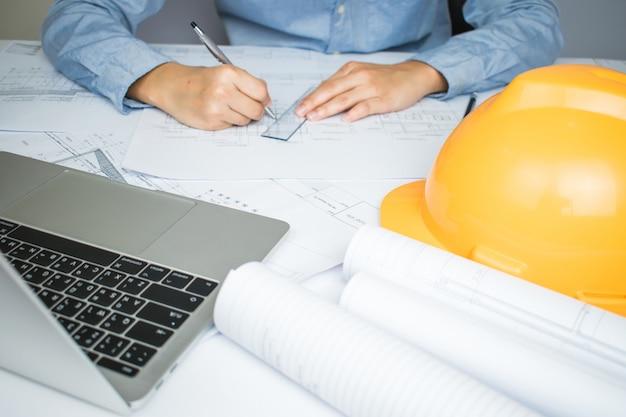 Dichter bij de handen van ingenieurs die werken aan blauwdrukken die het huisplan op het bureau ontwerpt