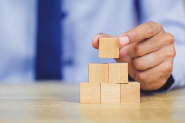 Dichter handen van zakenlieden, houten blokken stapelen in stappen.