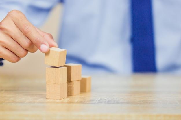 Dichter handen van zakenlieden, houten blokken stapelen in stappen