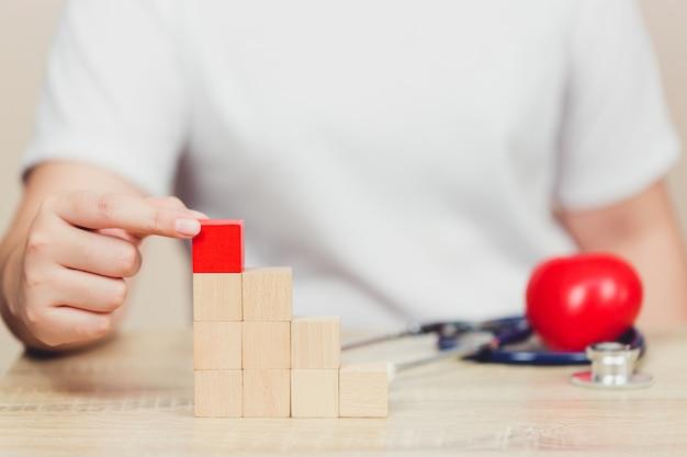 Dichtere handen van zakenlieden, die houten blokken stapelen in stappen, concept bedrijfs de groeisucces