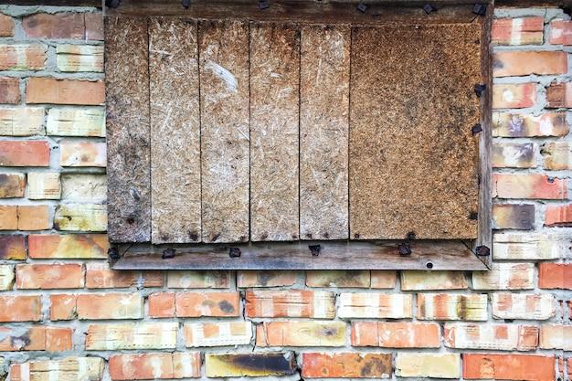 Dichtgetimmerd raam in verlaten oude bakstenen muur in schuur of gesloten oud huis. detailopname. buitenshuis.