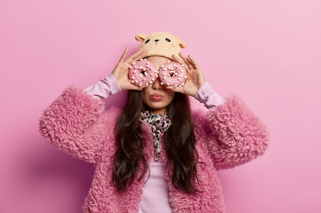 Dieet, calorieën, gewichtsverlies en verleiding concept. brunette vrouw houdt twee zoete geglazuurde donuts in de buurt van ogen, heeft een speelse bui, honger, draagt roze jas en hoed