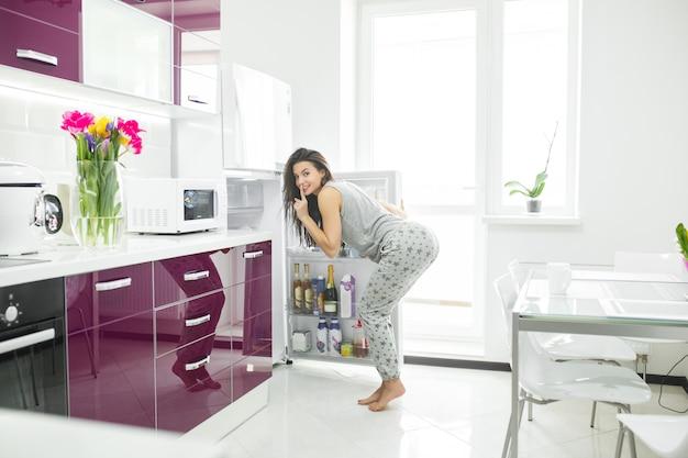 Dieet cheater. vrouw op de keuken dichtbij de koelkast. vrouw wil eten. hongerige dame in de ochtend.