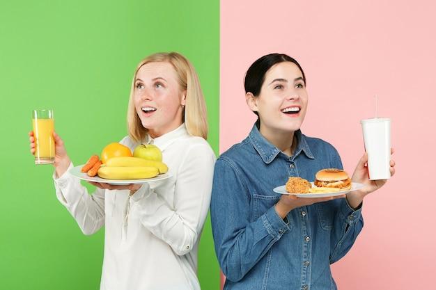 Dieet concept. gezond, nuttig voedsel. mooie jonge vrouwen kiezen tussen fruit en ongezond fastfood in de studio. menselijke emoties en vergelijkingsconcepten