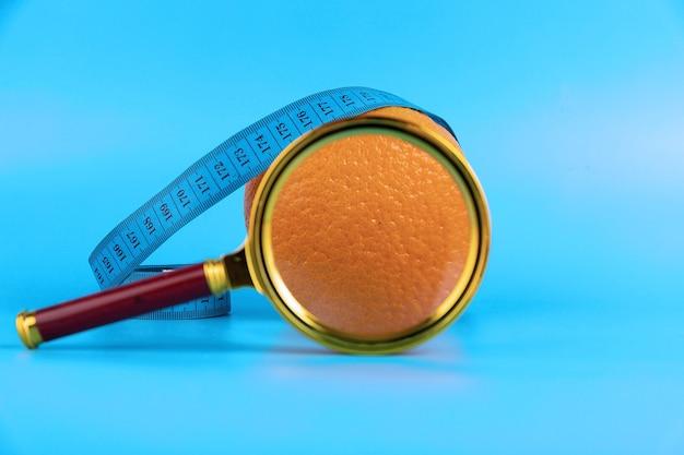 Dieet concept met meetlint, sinaasappel en vergrootglas voor gewichtsverlies op blauwe achtergrond.