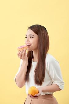 Dieet concept. mooie jonge aziatische vrouw met sinaasappel en donut over gele achtergrond. kiezen tussen junkfood en gezond eten.