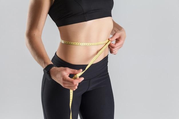 Dieet concept perfecte maag vrouw met centimeter