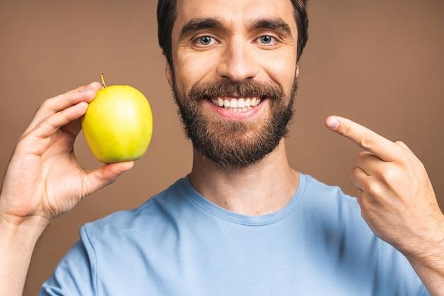 Dieet concept. vrolijke mooie bebaarde jonge man die groene appel eet, geïsoleerd op beige achtergrond.