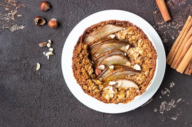 Dieet crumble met havermout, kaneel en peren versierd met hazelnoot en honing.