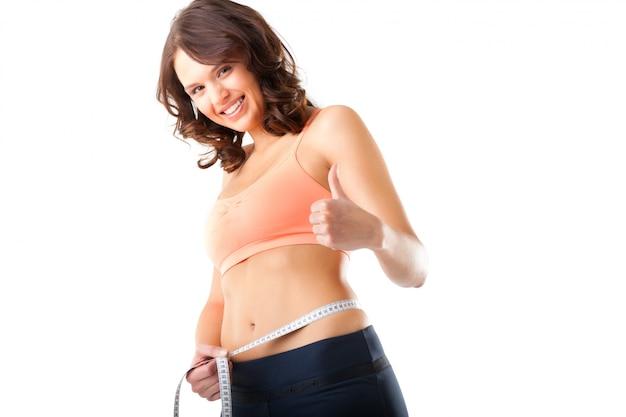 Dieet - de jonge vrouw meet haar taille