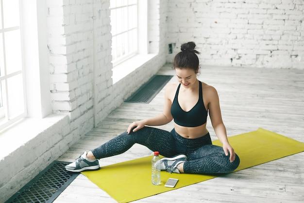 Dieet en fitness concept. vrolijke schattig meisje in trendy sportkleding zittend bij raam en glimlachend vrolijk, kijkend naar scherm van slimme telefoon liggend op groene mat voor haar, sms-bericht lezen