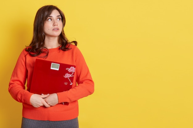 Dieet en gewicht, jonge gefrustreerde vrouw, opzij kijkend met peinzende gezichtsuitdrukking, zich ongezond voelen, mechanische weegschalen omhelzend, oranje trui dragen, poseert over geel.