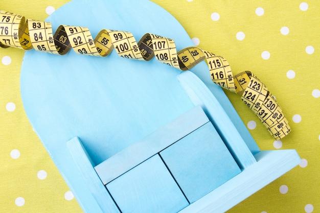 Dieet en gewichtsverlies concept blauwe speelgoedmeubels en meetlint op gele gestippelde achtergrond