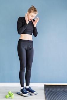 Dieet en gewichtsverlies. jonge verraste vrouw in zwarte sportkleren die zich op schalen bevinden