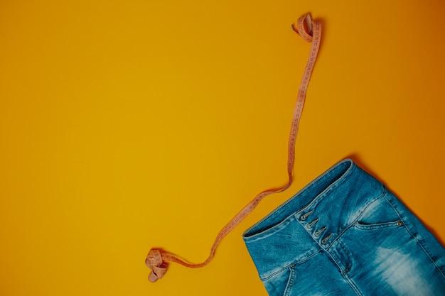 Dieet en gewichtsverlies thema. jeans en oranje meetlint met exemplaarruimte.