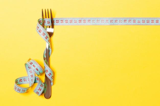 Dieet en gezond eten. vork en meetlint op gele achtergrond.