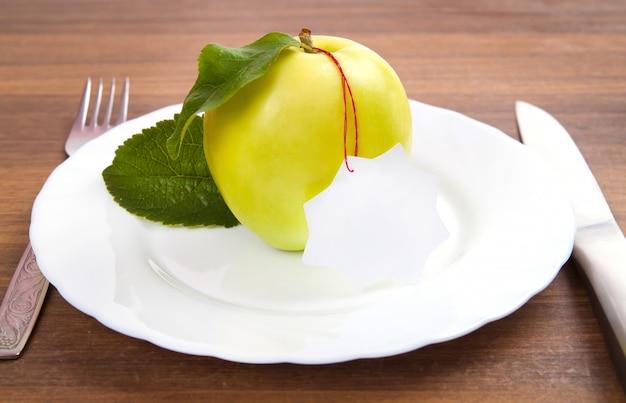 Dieet en gezonde voeding. geel, groene appel met blad en witte ticker