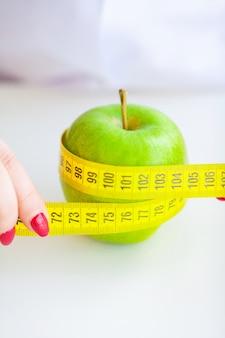 Dieet. fitness en gezond voedsel dieet concept. uitgebalanceerd dieet met groenten. portret van vrolijke artsenvoedingsdeskundige die groene appel in haar bureau meten. concept natuurlijk voedsel en gezonde levensstijl.