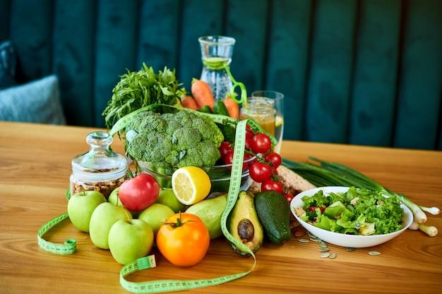 Dieet gewichtsverlies ontbijt concept met meetlint, biologische groenten, fruit, salade en zoet water. gezonde voeding concept, levensstijl en eten