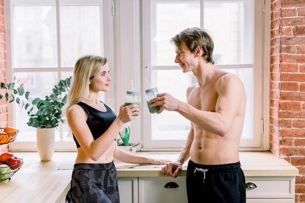 Dieet, gezond eten, fitness levensstijl, goede voeding. jong paar vegetariërs die verse smoothie op de keuken thuis drinken