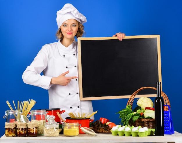 Dieet gezonde levensstijl vrouw chef-kok wijst op een bord gezond menu kitchener geïsoleerd op blue