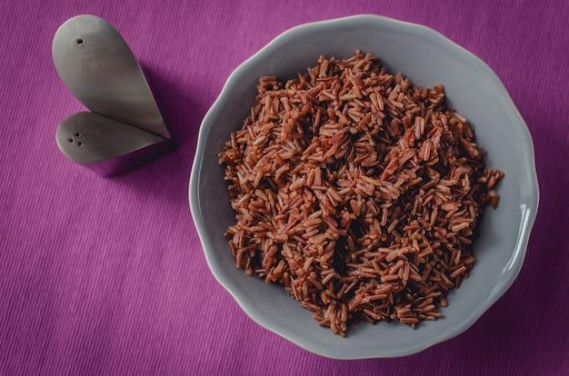 Dieet goede voeding. een plaat van bruine rijst op een mooie paarse tafel