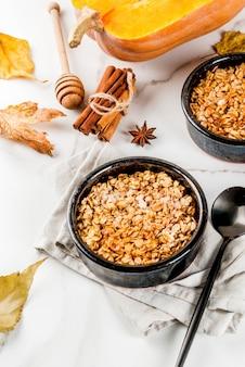 Dieet herfstgebak, ontbijt. crumble-pompoentaart, ahornsiroop en havermoutvlokken, in schoteltjes, op een witte marmeren tafel. kopieer ruimte