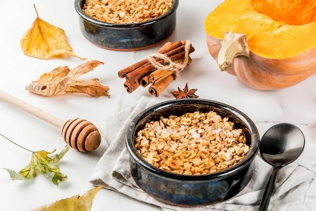 Dieet herfstgebak, ontbijt. crumble-pompoentaart, ahornsiroop en havermoutvlokken, in schoteltjes, op een witte marmeren tafel.