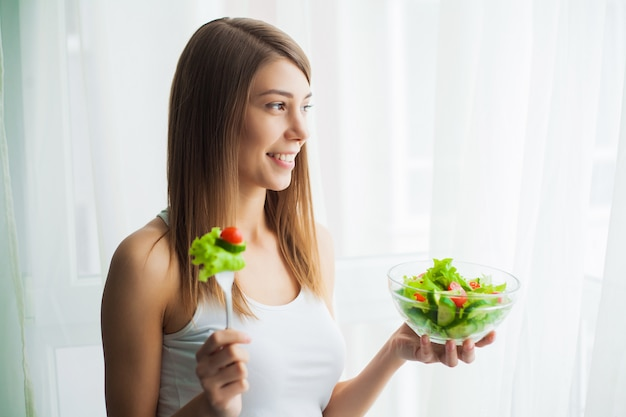 Dieet. jonge vrouw die salade eet en een gemengde salade houdt